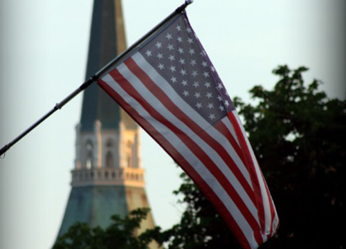 American flag with church in background